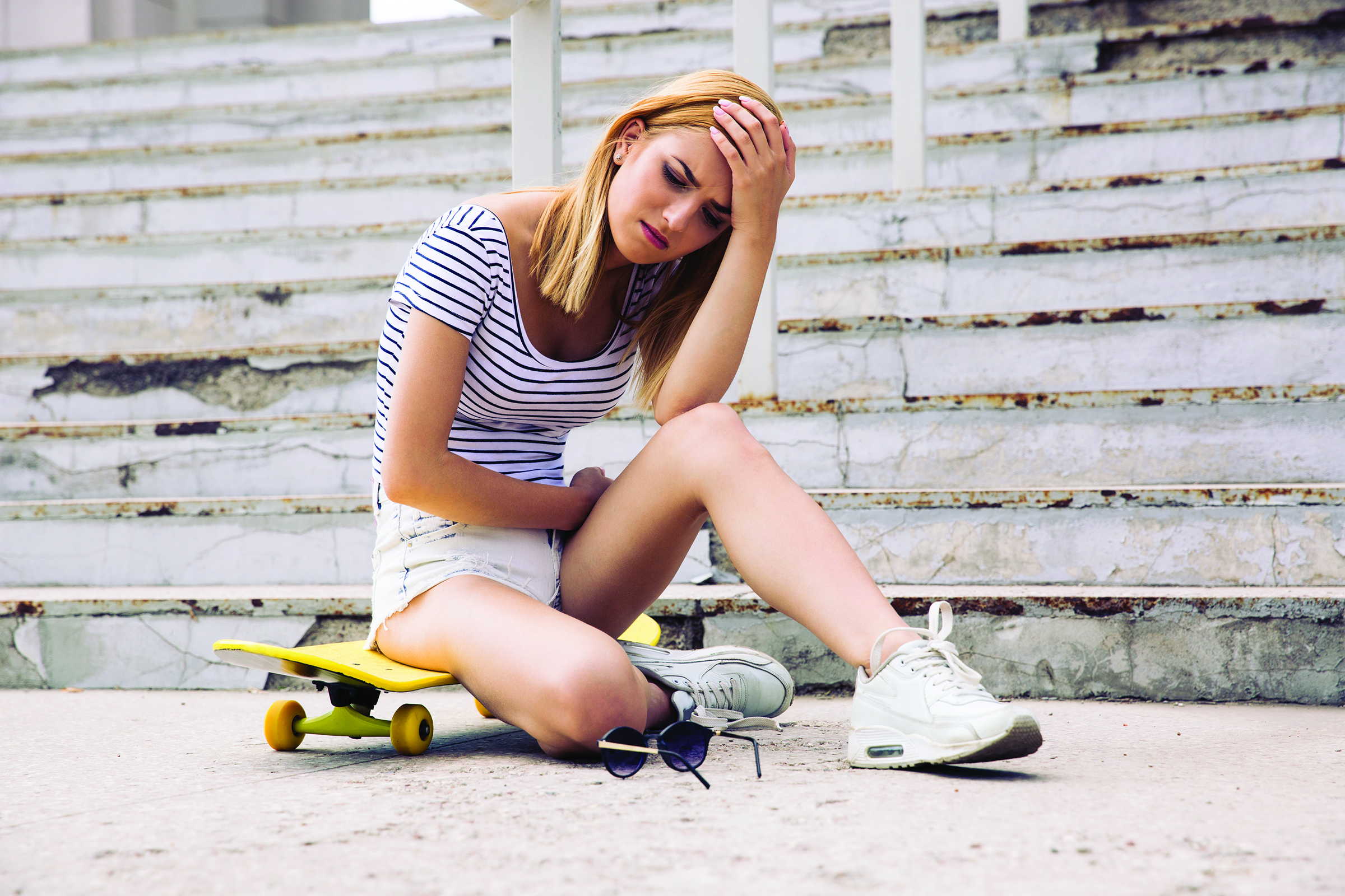Young female skater having headache outdoors
